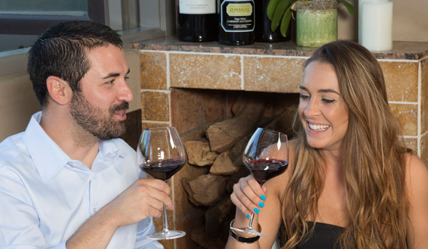 Couple enjoying wine in front of fireplace